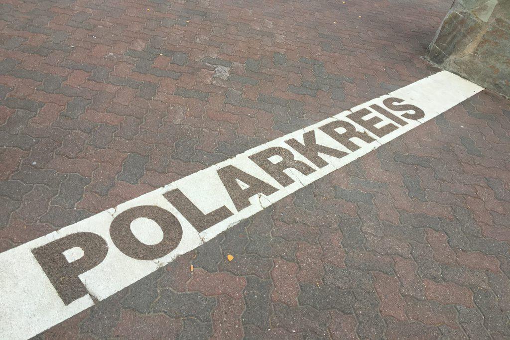 Die Polarkreis-Grenze ist auf dem Boden markiert und verläuft durch das Santa Claus Dorf.