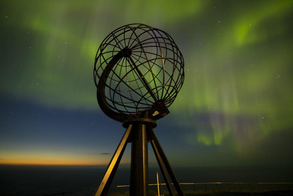Die Weltkugel umgeben von Nordlichtern.